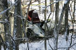 The wreckage of a twin-engine Piper Seneca PA-34 lies twisted among trees Jan. 31 where it crashed near the Huntington Tri-State Airport at Kenova, W. Va.. All six people on board died in the crash.