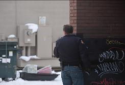 Aspen police officer Bill Linn pears from behind a wall at a sled containing wrapped packages left in an alleyway between Hopkins and Hyman Avenue in Downtown Aspen. Authorities recieved a tip alleging that explosives were placed in proximity of the Wells Fargo Aspen branch at 119 S. Mill St. and near the Vectra Bank Aspen branch at 534 E. Hyman Ave. Emergency responders shut down the downtown core to vehicles and set a large perimeter around several blocks.