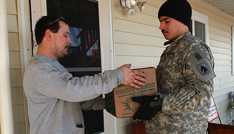 Henry Mudd, left, takes a case of Meals, Ready-to-Eat from Guardsman Drake Meyer on Sunday near Caneyville, Ky.