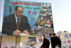 Iraqi men pass an election billboard showing Prime Minister Nouri al-Maliki. Unofficial results indicate allies of al-Maliki made gains in provincial elections Saturday.
