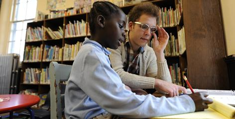 Ben Ansfield tutors Miatu Kormah, 8, at the Darby (Pa.) Free Library, slated to shut down.