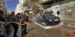 Palestinian fire-fighters use water to clean blood from the the street as Palestinians gather around a car hit in an Israeli missile strike on Feb. 2, in the Rafah refugee camp, southern Gaza Strip.