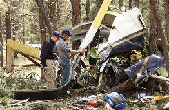 Federal workers review fatal crash site in Flagstaff, Ariz., on June 30, 2008. Two helicopters collided while flying to a hospital. Seven people died.