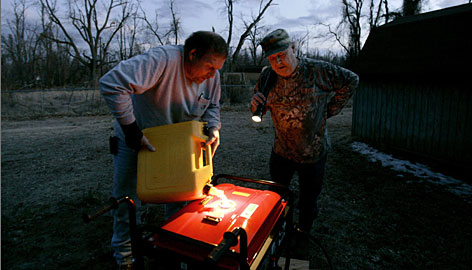 David Strange, left, fills Jimmy Timmons' portable generator with fuel on Sunday in Columbus, Ky., after electric service to Timmons' house was knocked out following a winter storm. Strange has been traveling around western Kentucky since the storm, helping get generators to those in need and keep others up and running.