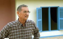 In this Nov. 19, 2004, file photo, Habitat for Humanity founder Millard Fuller poses at a home in Habitat's Global Village in Americus, Ga. Fuller died Tuesday after visiting a hospital in Americus, Ga., according to his wife, Linda. He was 74.