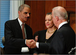 Vice President Biden swears in Eric Holder as U.S. attorney general on Tuesday at the Justice Dpeartment offices Washington. Holder's wife, Sharon, stands between the two.