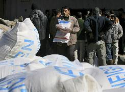 A Palestinian carries sacks of flour he received at a United Nations food distribution center in Rafah refugee camp in the southern of Gaza Strip. Hamas police in Gaza seized thousands of blankets and food parcels meant for needy residents.
