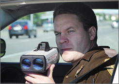 North Dakota State Trooper Jamey Jahner measures the speed of vehicles with a laser gun on Interstate 94 in Fargo.