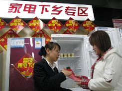 "Liu Yadan, right, discusses a refrigerator purchase with Shang Hongyu, manager of the Suning appliance store in Tongzhou, China. ""This policy is a kind of social welfare,"" Shang says."