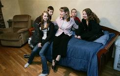 Debra Newton sits on her on the living room sofa with her four children, from left, Rebecca, 14, Alan, 11, Michael, 9, and Danielle, 16, in Hudson, N.H. She sent her oldest to a private kindergarten in 1998 but had to home-school her other children their kindergarten year for financial reasons. Private kindergarten costs $4,000 to $8,000 a year per child in Hudson, according to David Alukonis, chairman of the school board.