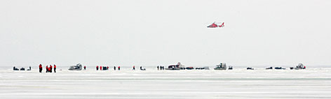 A helicopter flies over fishermen stranded on a slab of ice about 8 miles wide that broke free and floated away from the Ohio shoreline of Lake Erie, at Oak Harbor, Ohio, Saturday.