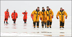 Rescue workers walk across frozen Lake Erie as they return to shore at Crane Creek State Park in Oak Harbor, Mich., after rescuing some of the fishermen stranded on a slab of ice about 1,000 yards off shore.