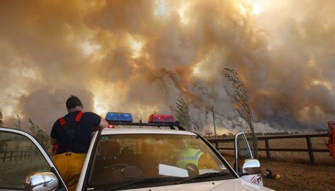 A firefighter pauses Saturday as a brush fire approaches the town of Labertouche, 56 miles east of Melbourne.
