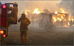 Volunteer firefighters prepare to move to another house as a barn burns close by in Melbourne on Saturday.