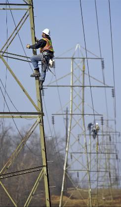 A utility worker from Michigan helps repair a power line in Free Union, Ky.