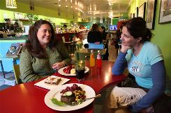 Carrie Morse, left, and restaurant owner Reem Azoury share a few laughs at Figs Fine Foods in Washington, D.C. Morse is a cancer survivor who ate regularly at Figs while in treatment at a local hospital.