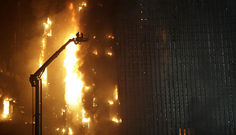 Firefighters battle a blaze in the 44-story building adjacent to China Central Television?s new headquarters complex in downtown Beijing.