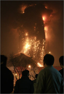 A crowd watches as the nearly finished Mandarin Oriental Hotel burns in Beijing on Monday night.