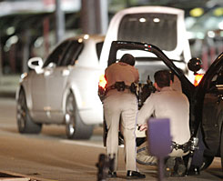 California Highway Patrol officers take cover behind a cruiser door with weapons drawn as they watch a suspect vehicle with its trunk open in Los Angeles on Tuesday. An assault suspect lead police on a slow-speed chase that ended in the North Hollywood section of Los Angeles. The suspect shot himself in the head in the car.