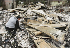 Residents have begun returning to their homes in Australia, where wildfires have destroyed homes and left dozens dead. Here, a woman picks through the remains of her home in Flowerdale, north of Melbourne.
