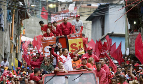 "Venezuelan President Hugo Chavez, in white, greets supporters as he campaigns Saturday in Caracas for ""yes"" votes in Sunday's referendum. Venezuelans will vote on a proposed change to the constitution that would allow Chavez and other politicians to stay in office as long as they kept winning elections."