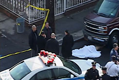 Police investigate the body of Guido Salvador Carabajo-Jara, 26, under a van in the Coney Island neighborhood of Brooklyn, N.Y., on Wednesday. The man was hit by an SUV in Queens, then swept under the van and dragged nearly 20 miles on New York City highways before the driver discovered the body in Brooklyn.