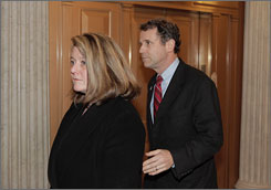 Sen. Sherrod Brown, D-Ohio, right, arrives at the Capitol in Washington from his mother's wake in Ohio to cast the final vote on the stimulus bill on Friday night. With him is his wife, Connie Schultz.