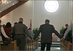 Worshipers hold hands during a church service Sunday at Clarence Center United Methodist Church in memory of the victims of Thursday's plane crash in Clarence Center, N.Y.