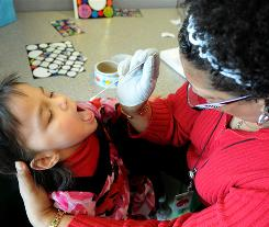 Epidemiologist Cynthia Hickman swabs the throat of Isabella Ventocilla, 4, in a study to see how many children may be carrying Hib.