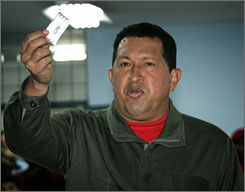 Venezuela's President Hugo Chavez shows his ballot before voting on a constitutional amendment referendum at a polling station in Caracas on Sunday.
