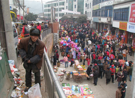 An old man sorts through rubbish looking for items to sell as crowds swarm Bamboo Pole to buy everything from firewater to firecrackers for Chinese new year's celebrations in January.
