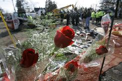 Flowers are left Monday by family members of plane crash victims at the scene of Thursday's tragedy in Clarence Center, N.Y.