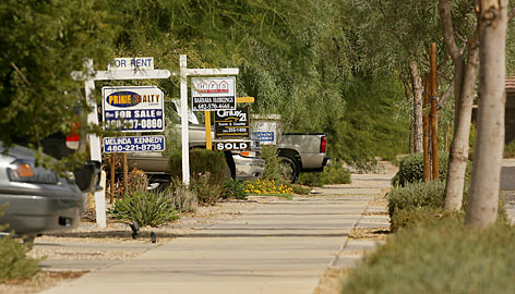 Real estate signs are posted in front of houses in Queen Creek, Ariz., in September 2007.