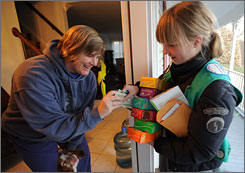 Girl Scout Billie Males, 12, of Troop 3377, delivers goods to Pam Jelinek in McLean, Va.