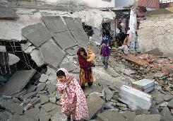 Children walk over debris at a school bombed by the Taliban last month in Swat Valley, Pakistan. The Pakistani government has stopped anti-Taliban offensives in the valley.