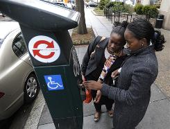 Marie Nzi, left, helps Mouna Konate figure out a smart meter on K Street in northwest Washington last week. Washington is installing new high-tech parking meters that will allow drivers to use credit cards.