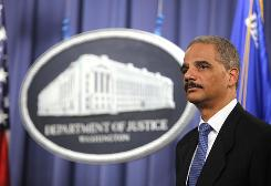 Attorney General Eric Holder listens during a news conference at the Justice Department in Washington.