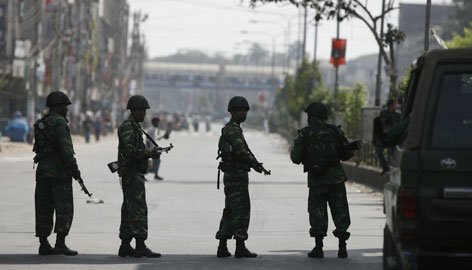 Army soldiers patrol in front of the Bangladesh Rifles headquarters in Dhaka Thursday after fresh gunfire erupted at a paramilitary camp after a deal with mutineers failed.