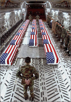 "Flag-draped coffins of U.S. troops sit aboard a cargo plane at Dover Air Force Base in Delaware. The anonymous coffins, or ""transfer cases,"" are each sealed in the Stars and Stripes and marked with a tag."