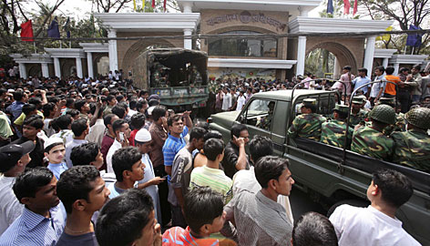 Bangladesh's Army soldiers enter the Bangladesh Rifles headquarters as hundreds of anxious people gather at Dhanmondi in Dhaka, Bangladesh, Friday.