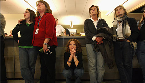 Rocky Mountain News copy editor Kim Humphreys, center, and fellow staffers watch a documentary about the newspaper before leaving the newsroom on their last day of work on Friday in Denver.