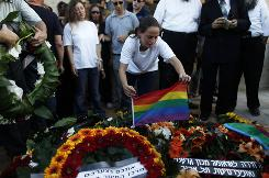 Chen Katz, a sister of Nir Katz who was killed during a shooting at a Tel Aviv gay club on Saturday, places a rainbow flag on his grave.