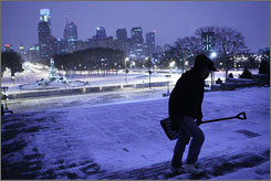 A woman walks up the steps of the Philadelphia Museum of Art early Monday as snow whipped through the Northeast.