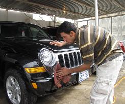 A Baghdad car lot worker cleans a Jeep.