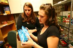 Metropolitan State College students, from left, Natalie Romero, 24, and Brittany Pyle, 21, distribute food and personal care items to college students in the student union building in Denver. During the fall semester, the food bank logged 443 student visits and so far this semester, the food bank has logged more than 480 student visits.