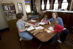 Andrea Farrier sits at her kitchen table with her children, from left, Rachel, 8, Rebecca, 4, and Sarah, 2, as they do schoolwork in their home in Kalona, Iowa. Farrier does double-duty -- homeschooling her daughters and working part-time for her school district as a supervisory teacher for 23 other homeschool families.