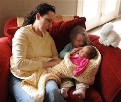 Patricia Bleignier-Baker watches as daughter Gracyn, 3, cradles baby sister Dylan in their Knoxville, Md., home. Both girls were conceived via in vitro fertilization. Bleignier-Baker opted for single-embryo transfer out of concern about the risks of multiple babies.