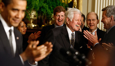 Sen. Edward Kennedy, who has been battling brain cancer, gets an ovation from President Obama and others as he arrives Thursday at the forum on overhauling the health care system.