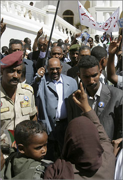 Sudanese President Omar al-Bashir walks through supporters after delivering a speech to thousands Thursday.