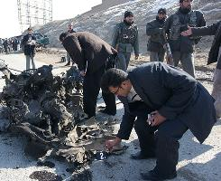 Afghan officials examine the scene on Feb. 1 after a suicide car bomber hit a convoy of foreign troops on the outskirts of Kabul, wounding two Afghan civilians and a French soldier, according to Afghan officials.